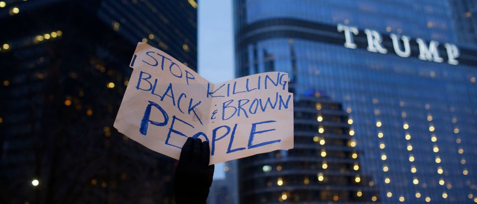 A demonstrator holds a sign during a protest near Trump International Hotel and Tower on April 2, 2018 in Chicago, Illinois in response to the police shooting of Stephon Clark in Sacramento, California and other victims of police shootings. - (Photo by Joshua Lott/AFP via Getty Images)