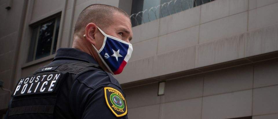 Police officer stands guard outside China's Consulate after employees left building in Houston, Texas