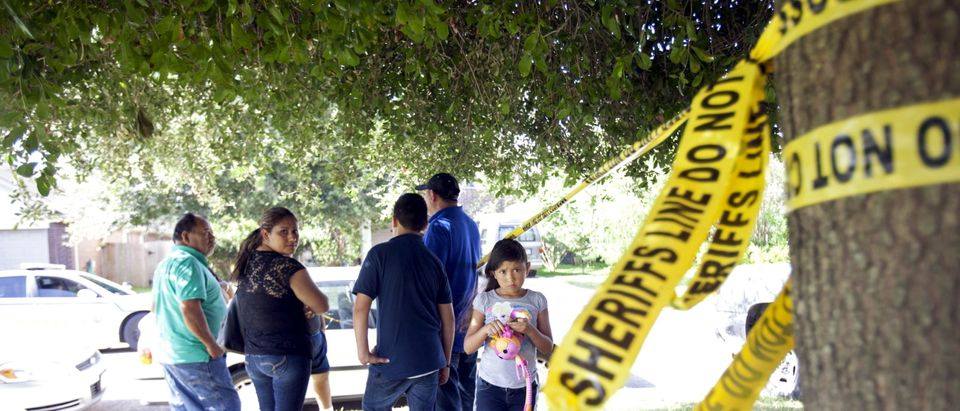 Neighbors gather behind police barrier tape at the scene of a shooting during which eight people were killed, in Houston, Texas