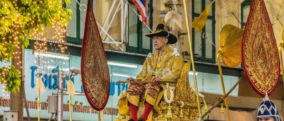 Thailand's King Maha Vajiralongkorn in a golden palanquin during the coronation procession. By Camera_Bravo. Shutterstock.