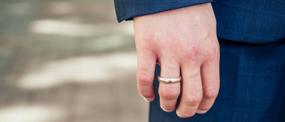 Wedding ring on a man's arm. Not the same man or ring in the story. By yurakrasil. Shutterstock