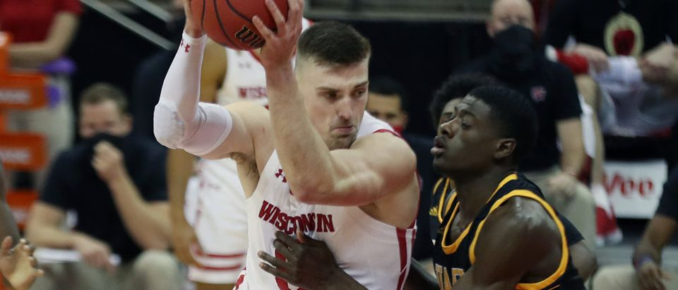 Nov 27, 2020; Madison, Wisconsin, USA; Wisconsin Badgers forward Micah Potter (11) drives against Arkansas-Pine Bluff Golden Lions forward Markedric Bell (right) at the Kohl Center. Mandatory Credit: Mary Langenfeld-USA TODAY Sports via Reuters