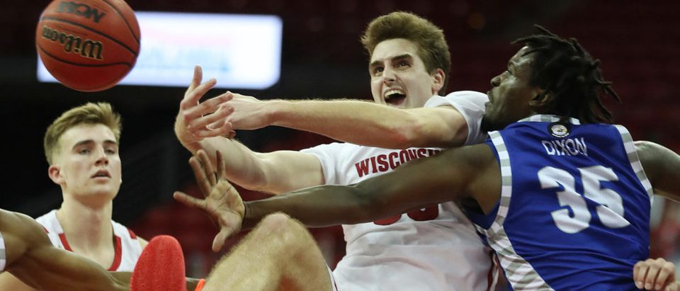 Nov 25, 2020; Madison, Wisconsin, USA; Wisconsin Badgers forward Nate Reuvers (middle) fights for a loose ball against Eastern Illinois Panthers guard George Dixon (35) at the Kohl Center. Mandatory Credit: Mary Langenfeld-USA TODAY Sports via Reuters