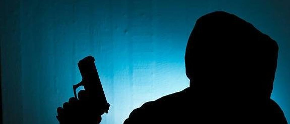 Silhouetted man with gun against blue wall background