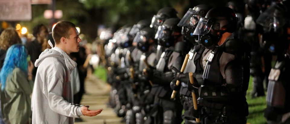 A protester pleads with riot police during nationwide unrest following the death in Minneapolis police custody of George Floyd, in Raleigh