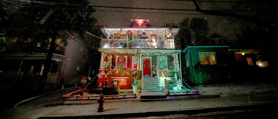 Snow falls around a house decorated for the Christmas holiday in Somerville