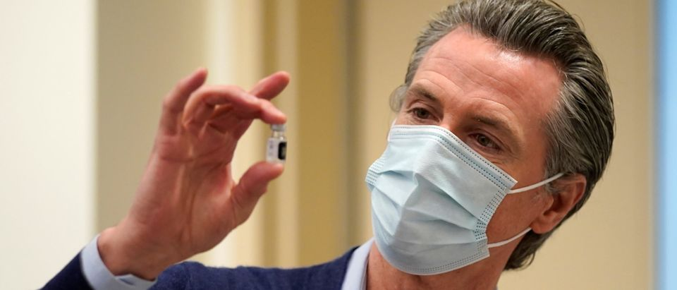 Gov. Gavin Newsom holds up a vial of the Pfizer-BioNTech COVID-19 vaccine at Kaiser Permanente Los Angeles Medical Center in Los Angeles