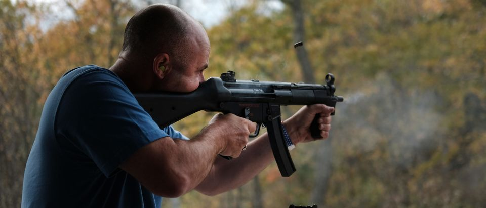 """GREELEY, PENNSYLVANIA - OCTOBER 12: A man shoots an automatic weapon at a shooting range during the """"Rod of Iron Freedom Festival"""" on October 12, 2019 in Greeley, Pennsylvania. The two-day event, which is organized by Kahr Arms/Tommy Gun Warehouse and Rod of Iron Ministries, has billed itself as a """"second amendment rally and celebration of freedom, faith and family."""" Numerous speakers, vendors and displays celebrated guns and gun culture in America. (Spencer Platt/Getty Images)"""
