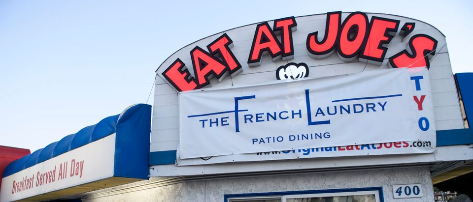 "An employee works inside the kitchen at ""Eat At Joe's"", which has remained open for outdoor dining in defiance of reimposed Los Angeles County Covid-19 restrictions in order to keep employees paid during the holidays, in Redondo Beach, California, December 1, 2020. - Owner Alex Jordan hung a ""French Laundry"" sign outside the restaurant following California Gov. Newsom's criticized former dinner at the Napa Valley restaurant. (Photo by Patrick T. Fallon/AFP via Getty Images)"