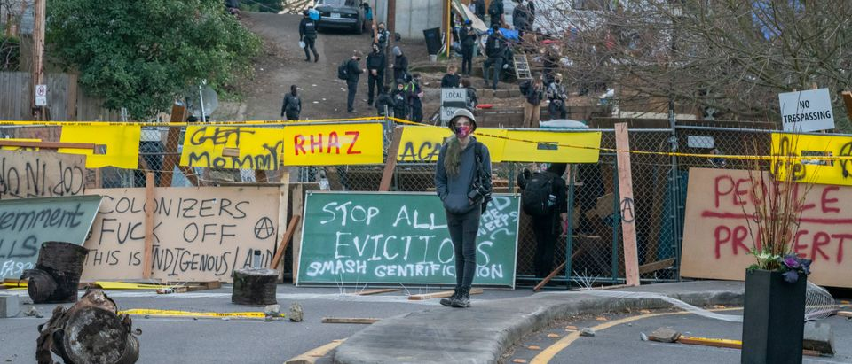 PORTLAND, OR - DECEMBER 09: An activists walks in front of barricades on December 9, 2020 in Portland, Oregon. Police and protesters clashed during an attempted eviction Tuesday, leading protesters to establish a barricade around the Red House. (Nathan Howard/Getty Images)