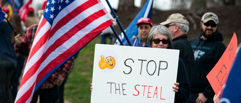 "STERLING, VA - DECEMBER 13: A supporter holds a sign that reads ""Stop the Steal"" outside Trump National Golf Club as U.S. President Donald Trump departs following a round of golf, on December 13, 2020 in Sterling, Virginia. (Al Drago/Getty Images)"