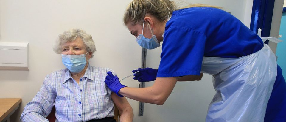 Nurse Practitioner Terri Welch (R) administers a dose of the Pfizer-BioNTech Covid-19 vaccine to a patient at the Haxby and Wigginton Group Medical Practice in Haxby, northern England on December 22, 2020. - Europe is expected to start a massive vaccination campaign after Christmas following the United States and Britain, which have begun giving jabs with an approved Pfizer-BioNTech shot, one of several leading candidates. (Photo by Lindsey Parnaby/AFP via Getty Images)