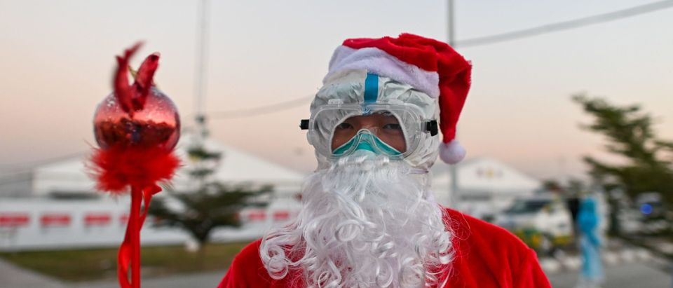 A healthcare worker dressed as Santa Claus prepares to distribute gifts to children at the Ayeyarwady Covid Centre in Mandalay, Myanmar, on December 25, 2020, Christmas Day, amid the Covid-19 pandemic, caused by the novel coronavirus. (Photo by Ye Aung Thu/AFP via Getty Images)
