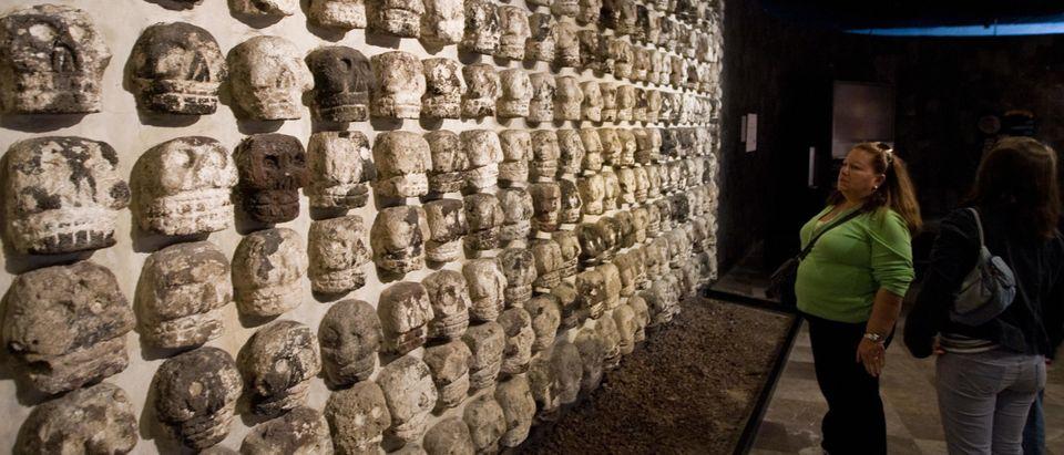 Women look at skull sculptures inside th