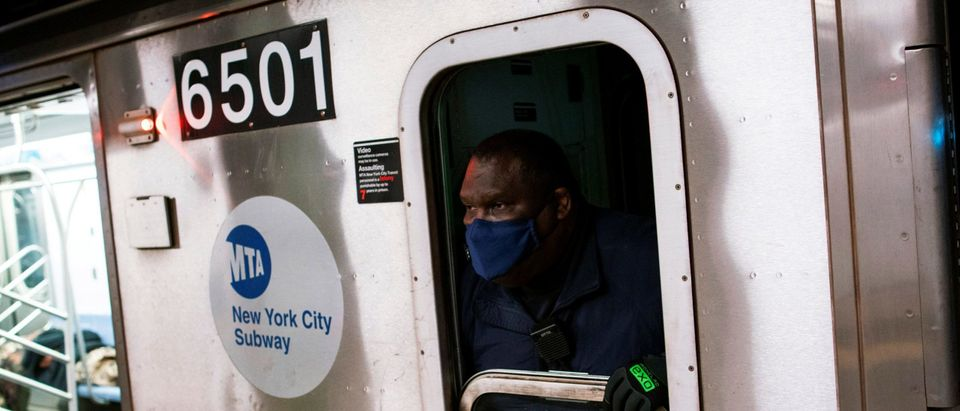 A worker of New York City The Metropolitan Transportation Authority (MTA) subway system, waits to close the door of the train during the morning rush, during the outbreak of the coronavirus disease (COVID-19) in New York City, New York