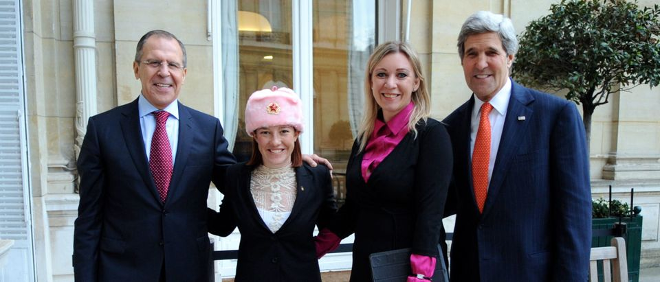 U.S. Department of State Spokesperson Jennifer Psaki -- sporting a shapka, or fur hat with ear flaps, given to her by Russian counterpart Maria Zakharova -- stands with Zakharova between U.S. Secretary of State John Kerry and Russian Foreign Minister Sergey Lavrov in Paris, France, on January 13, 2014. [State Department photo/ Public Domain]