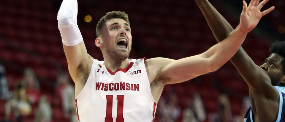 Dec 9, 2020; Madison, Wisconsin, USA; Wisconsin Badgers forward Micah Potter (11) goes up for a basket as Rhode Island Rams center Makhel Mitchell (22) defends during the first half at Kohl Center. Mandatory Credit: Mary Langenfeld-USA TODAY Sports via Reuters