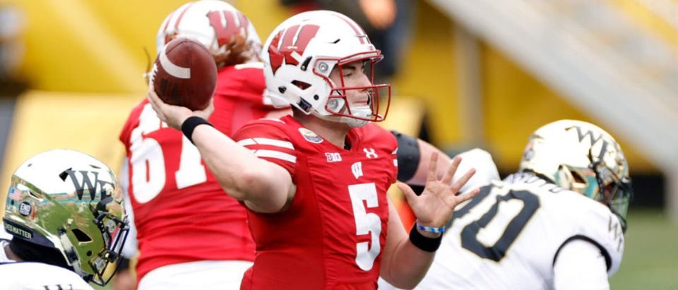 CHARLOTTE, NORTH CAROLINA - DECEMBER 30: Quarterback Graham Mertz #5 of the Wisconsin Badgers looks to pass against the Wake Forest Demon Deacons during the first half of the Duke's Mayo Bowl at Bank of America Stadium on December 30, 2020 in Charlotte, North Carolina. (Photo by Jared C. Tilton/Getty Images)