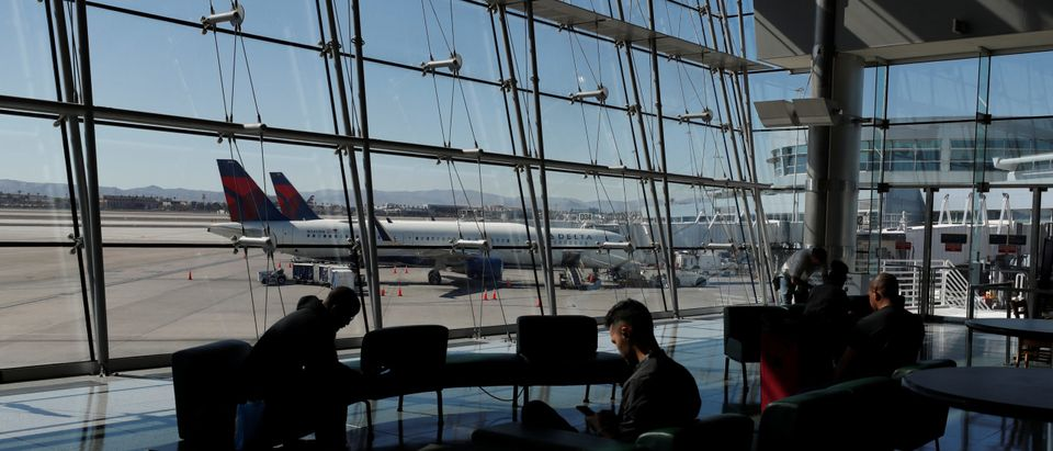 FILE PHOTO: Travelers sit in a lounge area as Delta Air Lines plane park at a gate in McCarran International Airport in Las Vegas