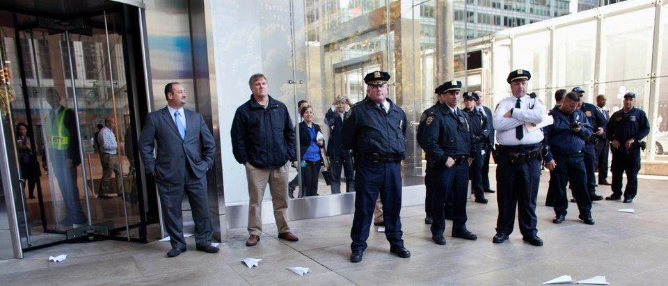 Paper airplanes, thrown by protesters affiliated with the Occupy Wall Street movement, are seen before police standing outside the Bank of America Building at 42nd Street and Sixth Avenue in New York
