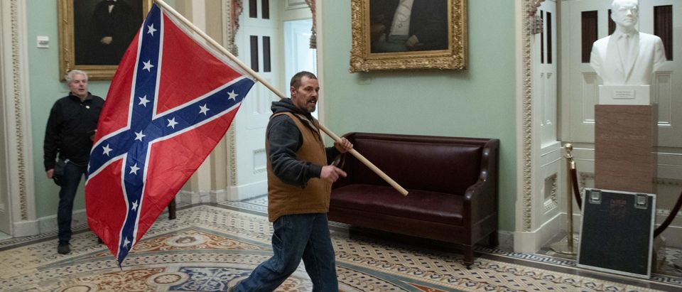 A supporter of US President Donald Trump carries a Confederate flag as he protestS in the US Capitol Rotunda on January 6, 2021, in Washington, DC. - Demonstrators breeched security and entered the Capitol as Congress debated the a 2020 presidential election Electoral Vote Certification. (Photo by Saul Loeb/AFP via Getty Images)