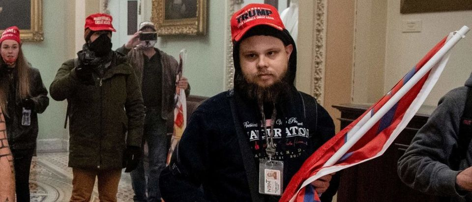 Supporters of US President Donald Trump, including Jake Angeli (C), a QAnon supporter known for his painted face and horned hat, enter the US Capitol on January 6, 2021, in Washington, DC. - Demonstrators breeched security and entered the Capitol as Congress debated the a 2020 presidential election Electoral Vote Certification. (Photo by Saul Loeb/AFP via Getty Images)