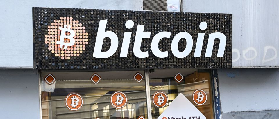 The reflection of a woman walking past a Bitcoin digital currency ATM shop in Marseille, southern France, on January 8, 2021. (Photo by Nicolas Tucat /AFP via Getty Images)
