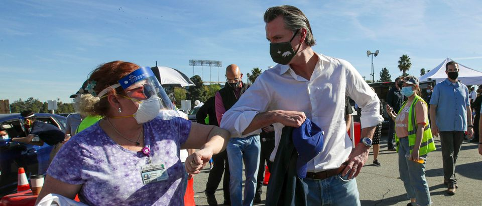 California Governor Gavin Newsom (R) is greeted by a healthcare worker at the launch of a mass Covid-19 vaccination site at Dodger Stadium on January 15, 2021 in Los Angeles, California. (Photo by Irfan Khan/AFP via Getty Images)