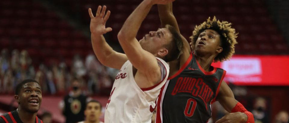 Jan 23, 2021; Madison, Wisconsin, USA; Ohio State Buckeyes guard Meechie Johnson Jr. (0) blocks a shot from Wisconsin Badgers guard Brad Davison (34) during the first half at the Kohl Center. Mandatory Credit: Mary Langenfeld-USA TODAY Sports via Reuters