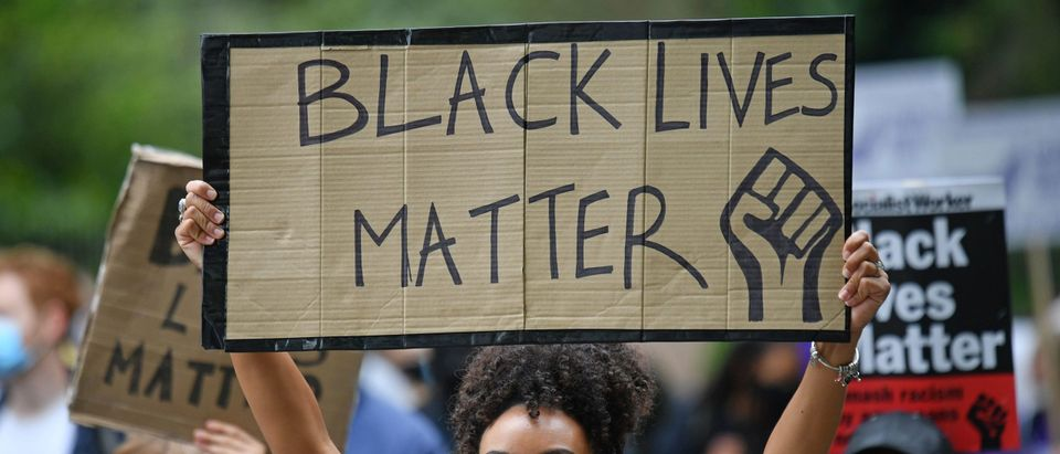 People hold up placards in support of the Black Lives Matter movement as they take part in the inaugural Million People March march from Notting Hill to Hyde Park in London on August 30, 2020.