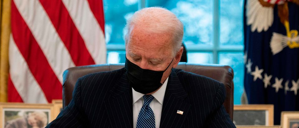 US President Joe Biden signs an Executive Order reversing Trump era ban on Transgender serving in the military while in the Oval Office of the White House in Washington, DC, on January 25, 2021. (JIM WATSON/AFP via Getty Images)