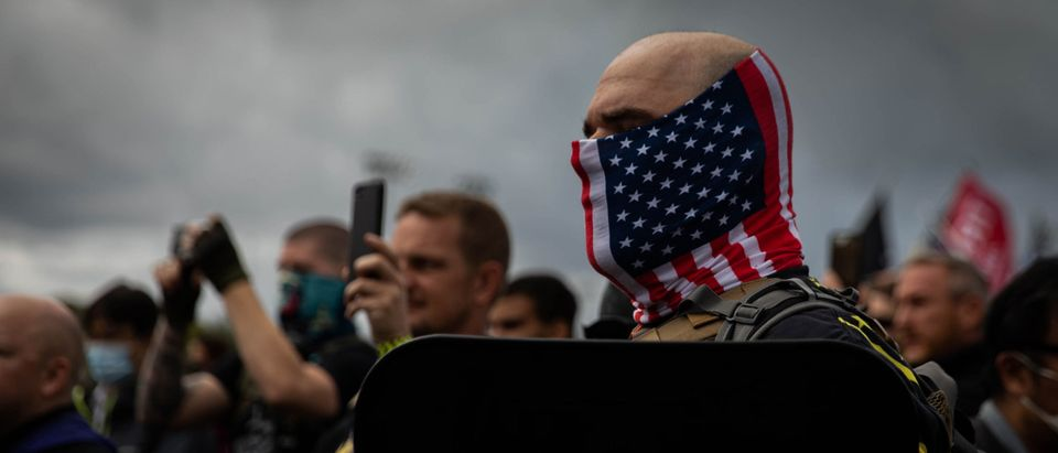 "A man hold his hand to his heart as a Proud Boys organizer recites the Pledge of Allegiance during a Proud Boys rally at Delta Park in Portland, Oregon on September 26, 2020. - Far-right group ""Proud Boys"" members gather in Portland to show support to US president Donald Trump and to condemn violence that have been occurring for more than three months during ""Black Lives Matter"" and ""Antifa"" protests. (Photo by Maranie R. Staab/AFP via Getty Images)"