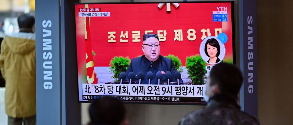 People watch a television screen showing news footage of North Korean leader Kim Jong Un