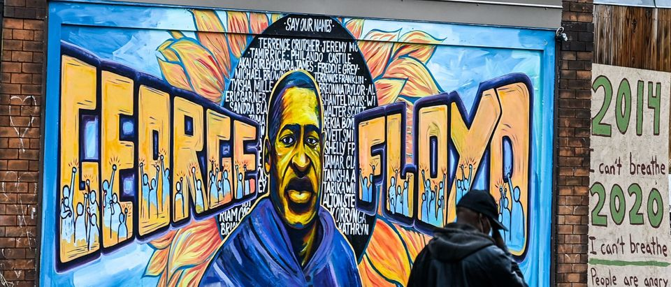 A man walks past the mural of George Floyd near the makeshift memorial of George Floyd before the third day of jury selection begins in the trial of former Minneapolis Police officer Derek Chauvin who is accused of killing Floyd, in Minneapolis, Minnesota on March 10, 2021. (CHANDAN KHANNA/AFP via Getty Images)