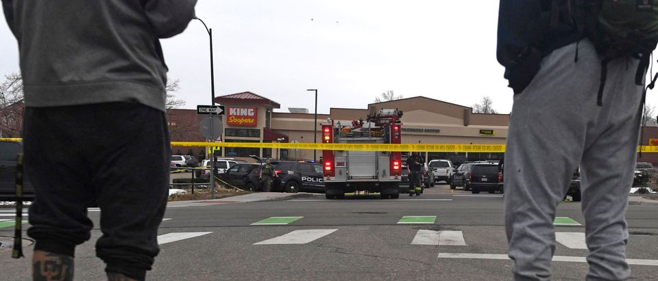 """Onlookers stand outside the King Soopers grocery store in Boulder, Colorado on March 22, 2021 after reports of an active shooter. - Police swarmed a grocery store in the western US state of Colorado on March 22, 2021, following reports of an active shooter and multiple casualties, law enforcement and eyewitnesses said, with at least one man detained. No details of casualties have been confirmed, but Colorado governor Jared Polis and Boulder Mayor Sam Weaver each referred to the incident as a """"tragedy"""" in statements on Twitter. (Photo by Jason Connolly/AFP via Getty Images)"""