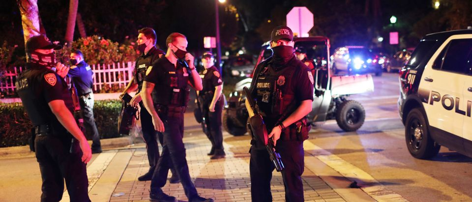 Miami Beach police officers direct people away from the area as an 8pm curfew is in place on March 21, 2021 in Miami Beach, Florida. (Photo by Joe Raedle/Getty Images)
