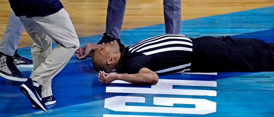 Mar 30, 2021; Indianapolis, IN, USA; Medical personnel take care of a NCAA referee after he fell on the court during the first half during the game between the Gonzaga Bulldogs and the USC Trojans in the Elite Eight of the 2021 NCAA Tournament at Lucas Oil Stadium. Mandatory Credit: Robert Deutsch-USA TODAY Sports via Reuters