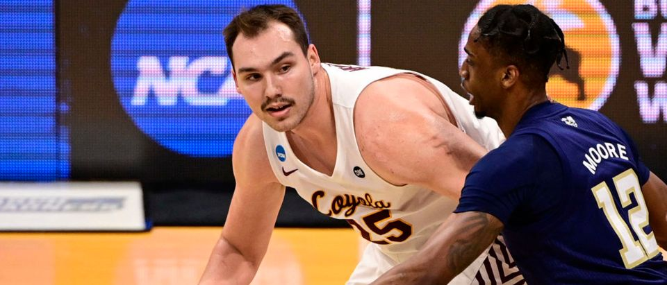 Mar 19, 2021; Indianapolis, Indiana, USA; Loyola Ramblers center Cameron Krutwig (25) dribbles the ball against Georgia Tech Yellow Jackets forward Khalid Moore (12) during the first round of the 2021 NCAA Tournament at Hinkle Fieldhouse. Mandatory Credit: Marc Lebryk-USA TODAY Sports via Reuters