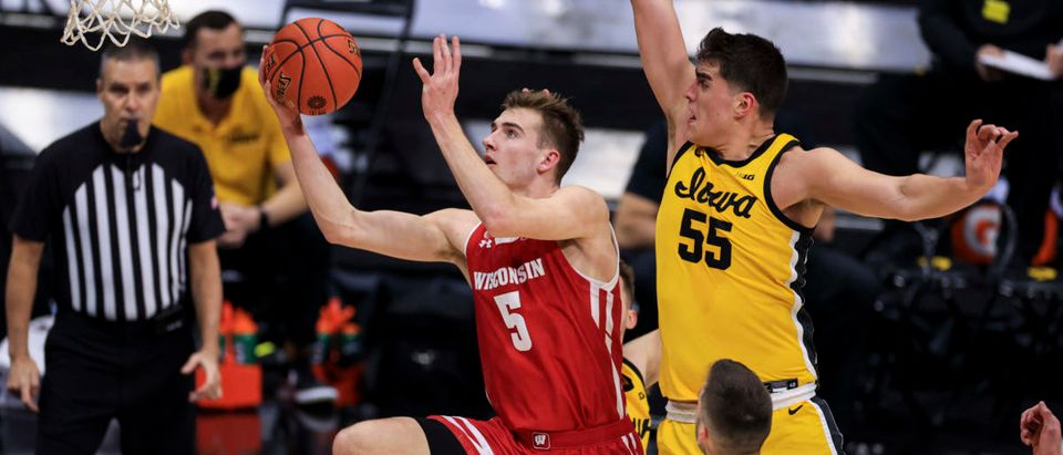 Mar 12, 2021; Indianapolis, Indiana, USA; Wisconsin Badgers forward Tyler Wahl (5) drives to the basket against Iowa Hawkeyes guard Connor McCaffery (30) and center Luka Garza (55) in the first half at Lucas Oil Stadium. Mandatory Credit: Aaron Doster-USA TODAY Sports via Reuters