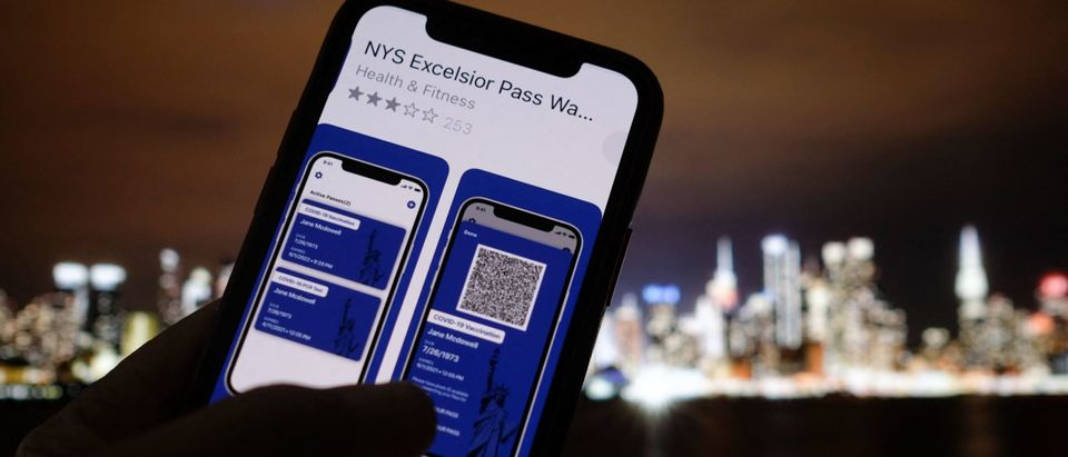 This illustration photo taken in Los Angeles on April 6, 2021 shows a person looking at the app for the New York State Excelsior Pass, which provides secure, digital proof of a Covid-19 vaccination, in front of a screen showing the New York skyline. - As the United States' vaccination campaign accelerates, so-called vaccine passports are gaining traction despite political divisions and a fragmented health care system that complicates the centralization of data. (Photo by Chris DELMAS / AFP) (Photo by CHRIS DELMAS/AFP via Getty Images)