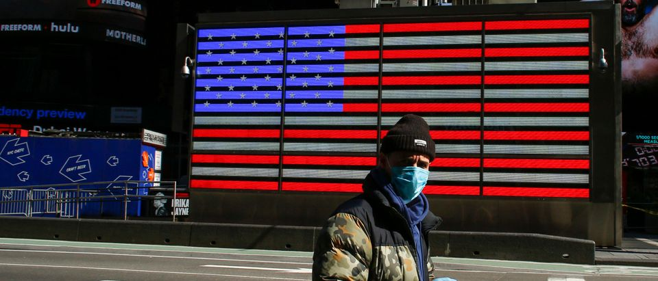 A man wears a face mask as he check his phone in Times Square on March 22, 2020 in New York City. - Coronavirus deaths soared across the United States and Europe on despite heightened restrictions as hospitals scrambled to find ventilators. (Photo by Kena Betancur/AFP via Getty Images)