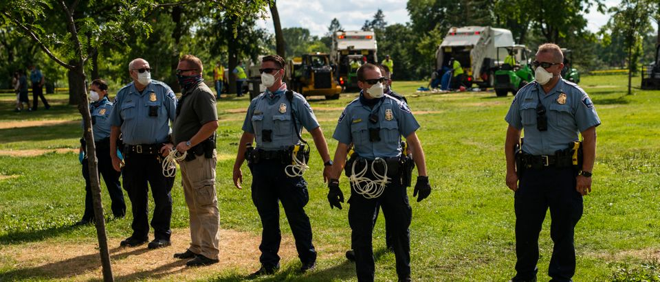 MINNEAPOLIS, MN - JULY 20: Minneapolis Police stand guard as a homeless encampment is cleared by crews in Powderhorn Park on July 20, 2020 in Minneapolis, Minnesota. (Stephen Maturen/Getty Images)