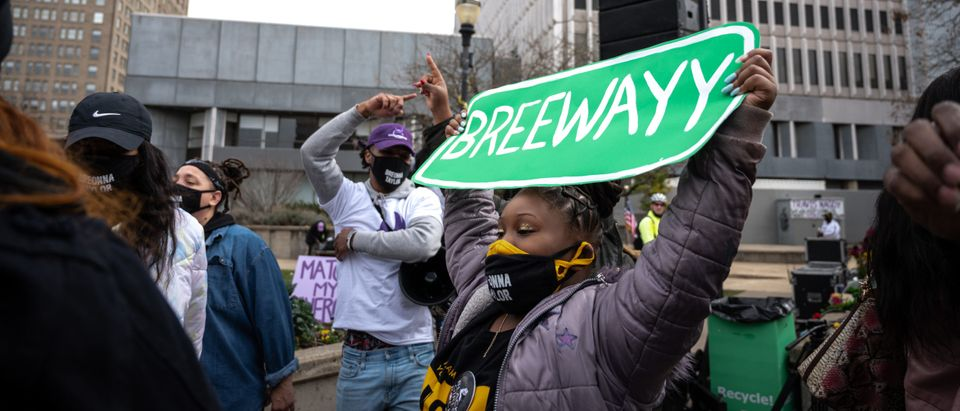 """LOUISVILLE, KY - MARCH 13: A child with a """"BREEWAYY"""" sign displays it for the crowd in Jefferson Square Park on March 13, 2021 in Louisville, Kentucky. (Jon Cherry/Getty Images)"""
