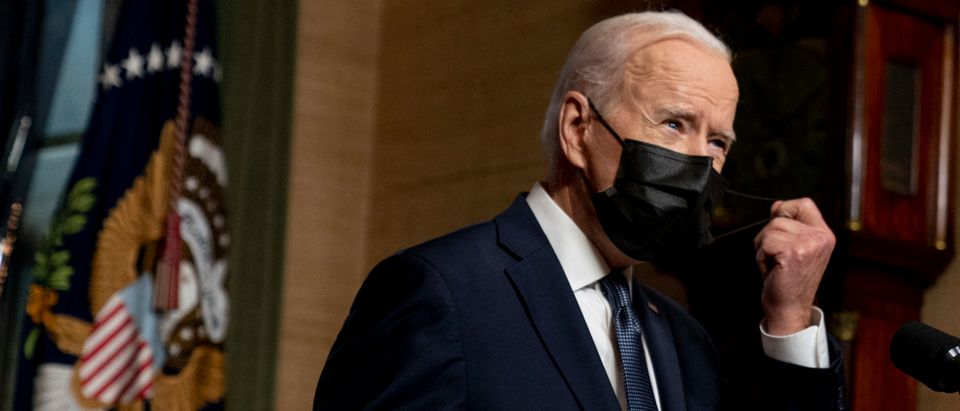 """US President Joe Biden removes his facemask before speaking from the Treaty Room in the White House on April 14, 2021 in Washington, DC, about the withdrawal of the remainder of US troops from Afghanistan. - President Joe Biden announced Wednesday it's """"time to end"""" America's longest war with the unconditional withdrawal of troops from Afghanistan, where they have spent two decades in a bloody, largely fruitless battle against the Taliban. (Photo by Andrew Harnik/POOL/AFP via Getty Images)"""