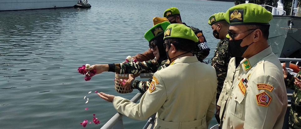 Naval officers throw flowers into the sea at the port of Semarang on April 26, 2021, as sign of respect for the submarine that disappeared off the coast of Bali and has been found cracked into pieces on the seafloor with all 53 crew killed in the disaster. (Photo by DAFFA RAMYA KANZUDDIN/AFP via Getty Images)
