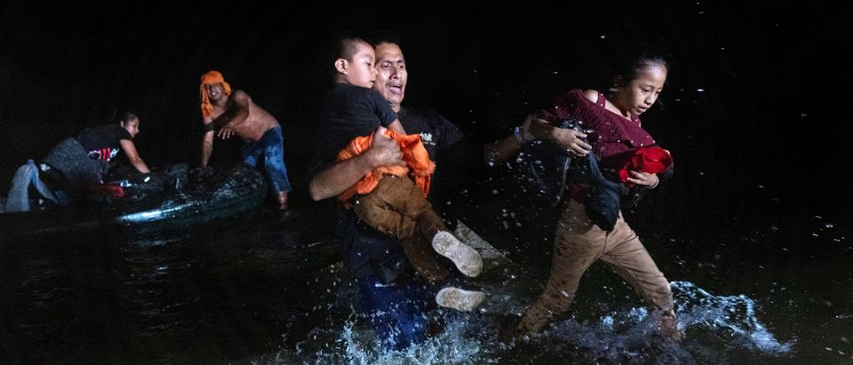 ROMA, TEXAS - APRIL 14: An immigrant father grips his children while walking ashore on the bank of the Rio Grande at the U.S.-Mexico border on April 14, 2021 in Roma, Texas. (John Moore/Getty Images)