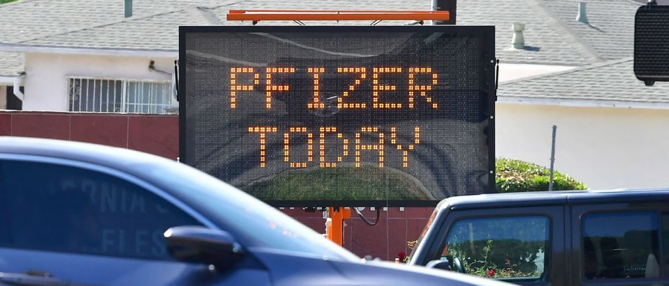 """Motorists make their way past a sign announcing """"Pfizer Today"""" available at the Cal State Los Angeles Covid-19 vaccine site in Los Angeles, California on May 3, 2021. - A citywide emergency alert was due to be sent to cell phone in Los Angeles on Monday reminding people to get their Covid-19 vaccine as numbers of people getting vaccinated have fallen over the past week. The city-run vaccination sites are due to offer more than 250,000 doses this week, more than ever offered during the pandemic. (Photo by Frederic J. Brown/AFP via Getty Images)"""