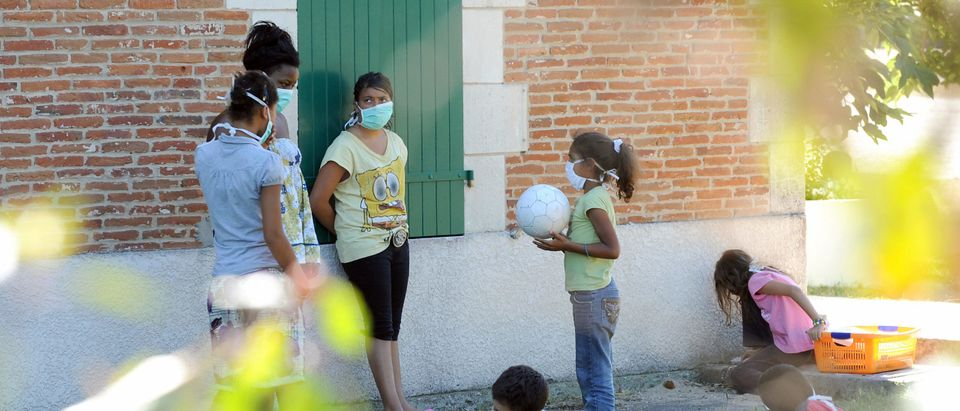 Children wearing masks play outdoors in