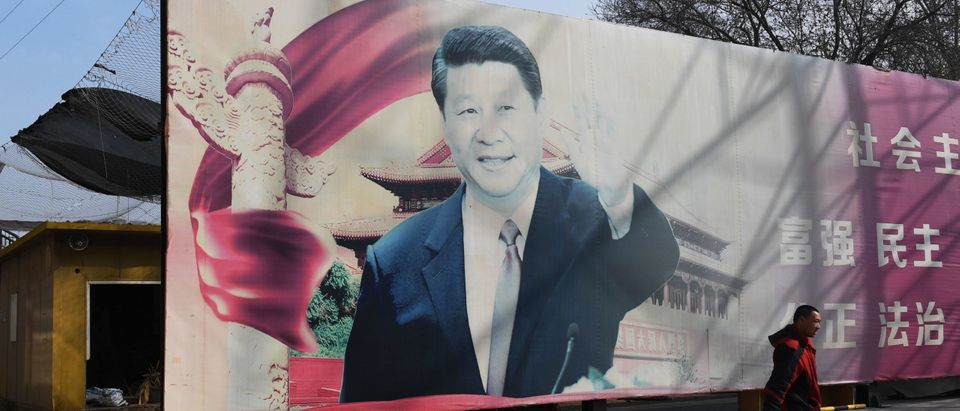 """A man walks past a faded propaganda billboard featuring an image of China's President Xi Jinping, in a car park in Beijing on March 19, 2018. Chinese President Xi Jinping on March 19 congratulated Russian counterpart Vladimir Putin on his re-election, saying Beijing was willing to work with Moscow to bring ties to a """"higher level"""". Putin won in a landslide on March 18, one day after China's parliament unanimously re-appointed Xi to a second term. (Photo by Greg Baker/AFP via Getty Images)"""