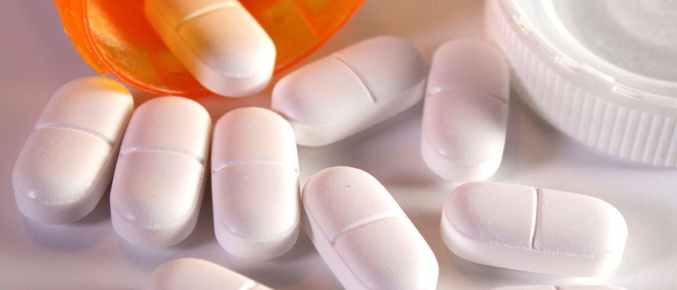 Prescription pain pills spilling out of bottle [Shutterstock]